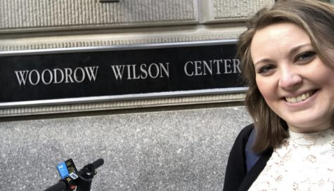 Olivia takes a selfie in front of The Wilson Center sign